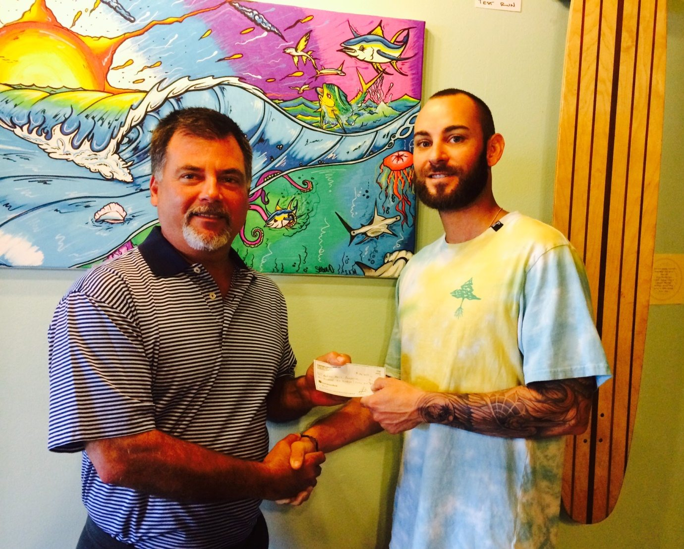 Drew Thompson of 3 Natives presenting Scott Harris with the $1,646 check from their Red Bowl Fundraiser